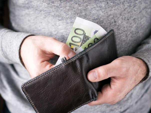 Pfändung beim Drittschuldner - Geldschein wird aus Portemonnaie gezogen