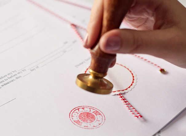 Forderungen titulieren lassen - Hand mit Stempel beim Notar