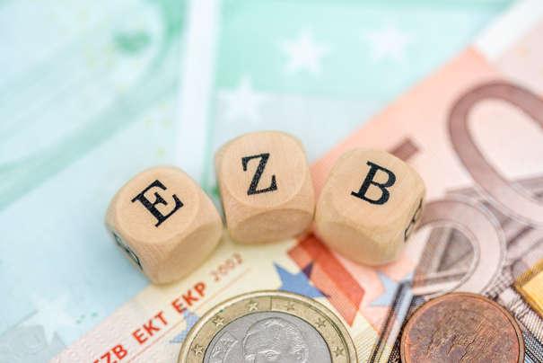Euromünze und Noten mit EZB Würfeln: Die EZB schafft die Grundlage für den Basiszinssatz