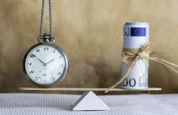 Uhr und Geld auf Waage - Bearbeitungszeit im Inkasso